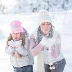 Cheerful family having fun outdoor in the snow. Little girl and her mother in winter time.