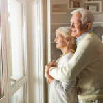 Senior couple looking out living room window